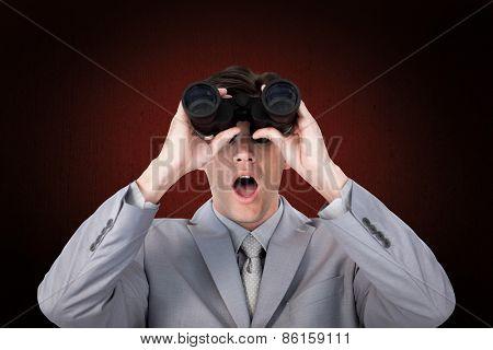 Suprised businessman looking through binoculars against weathered surface
