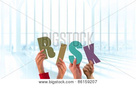 Hands holding up risk against white room with large window overlooking city