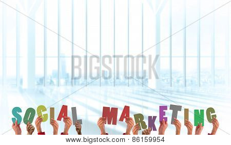 Hands holding up social marketing against white room with large window overlooking city