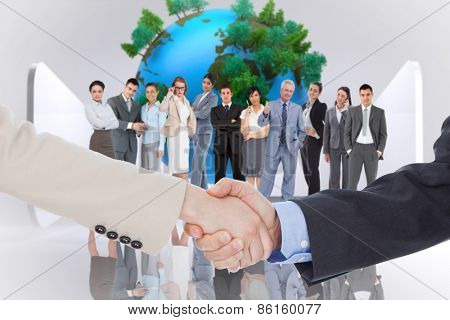 Smiling business people shaking hands while looking at the camera against earth on abstract grey background