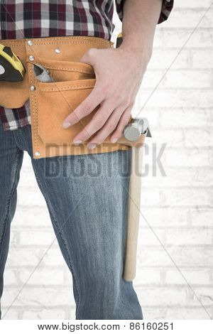 Handyman wearing tool belt against white wall