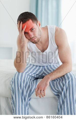 Portrait of a depressed man sitting on his bed while looking at the camera