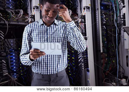 Young businessman thinking and holding tablet against data center