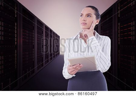 Confused businesswoman using a tablet pc against server hallway