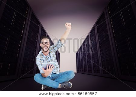 Handsome hipster using tablet pc and cheering against server hallway