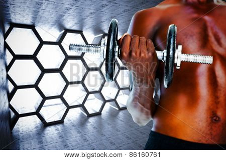 Mid section of fit shirtless man holding dumbbell against hexagon room