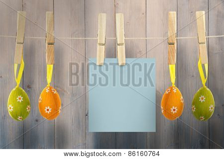 Hanging easter eggs and card against pale grey wooden planks