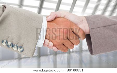 Side view of business peoples hands shaking against room with large window looking on city
