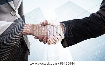 Close up of two businesspeople shaking their hands against skyscraper