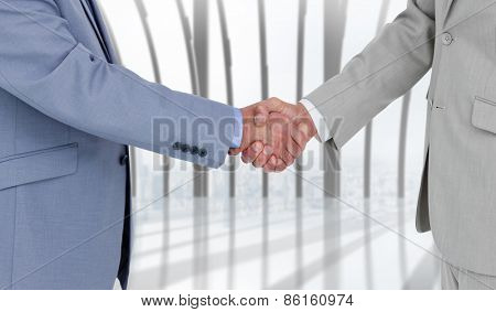 Side view of shaking hands against white room with large window overlooking city