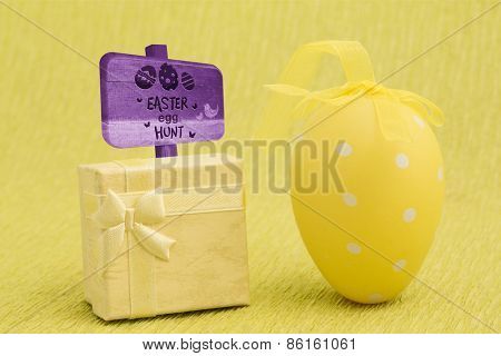 Easter egg hunt sign against yellow easter egg and present