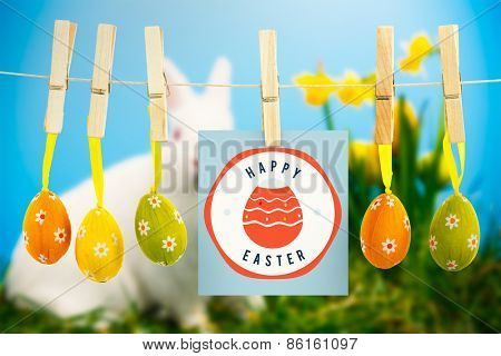 happy easter graphic against white fluffy bunny sitting beside daffodils with easter eggs
