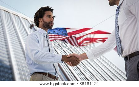 Young businessmen shaking hands in office against american flag and skyscraper