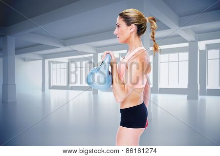 Female blonde crossfitter lifting kettlebell against white room with windows