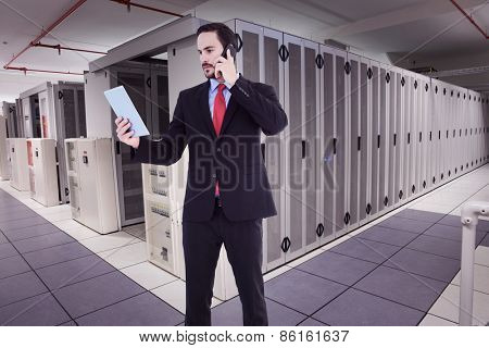 Businessman talking on phone holding tablet pc against data center