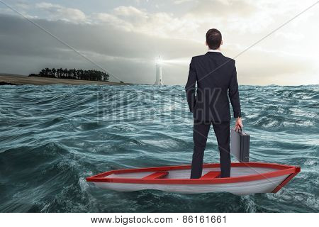 Businessman in boat against stormy sea with lighthouse