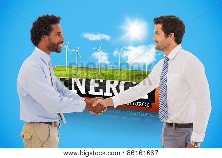 Smiling young businessmen shaking hands in office against wind turbine field in an energy saving battery