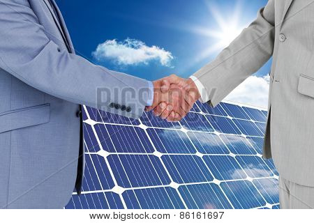 Side view of shaking hands against solar panel reflecting sunlight