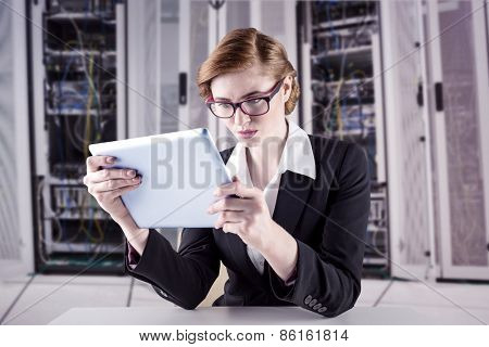 Redhead businesswoman using her tablet pc against data center