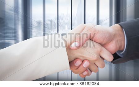 Close up on partners shaking hands against room with large window looking on city