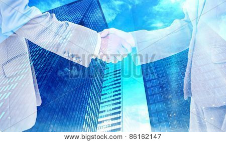 Side view of shaking hands against low angle view of skyscrapers