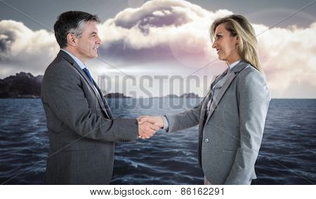 Pleased businessman shaking the hand of content businesswoman against calm sea with lighthouse
