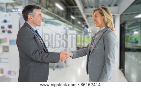 Pleased businessman shaking the hand of content businesswoman against college hallway