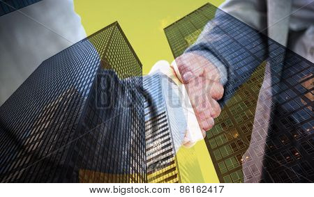 Business people shaking hands close up against skyscraper