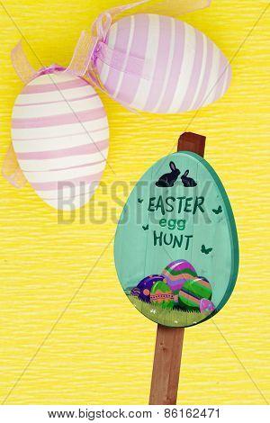 Easter egg hunt sign against two easter eggs