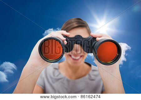 Woman looking through spyglasses against bright blue sky with clouds