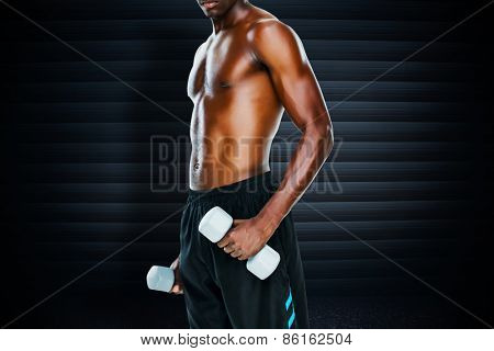Mid section of fit shirtless man lifting dumbbells against black background