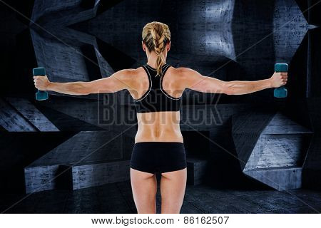 Female bodybuilder holding two dumbbells with arms out against dark room