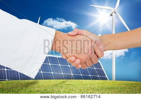 Extreme closeup of a doctor and patient shaking hands against large solar panel and three wind turbines