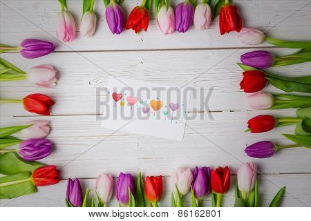 heart balloons against tulips on desk