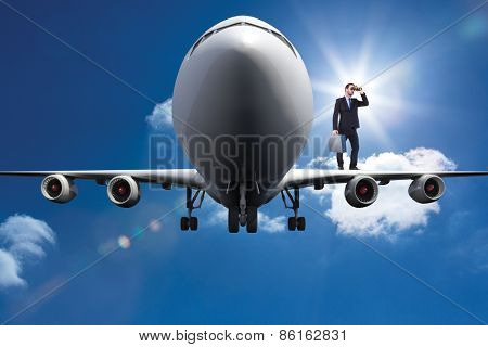 Businessman looking through binoculars holding briefcase against bright blue sky with clouds