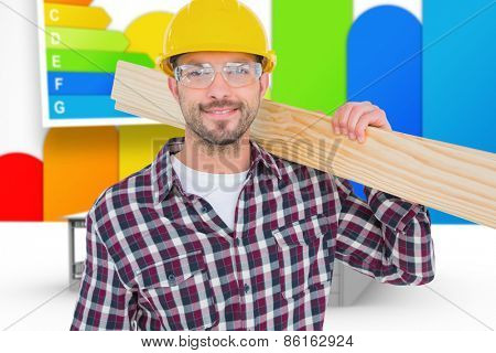 Handyman holding wood planks against house with energy rating background