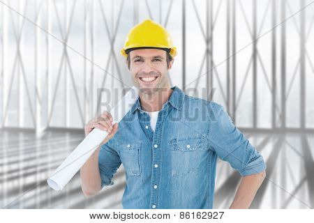 Confident architect holding rolled blueprint against white room with large window overlooking city