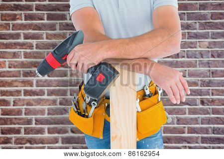 Midsection of male carpenter with power drill and plank against red brick wall