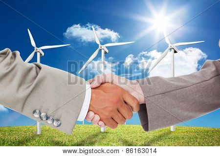 Side view of shaking hands against six wind turbines in a field