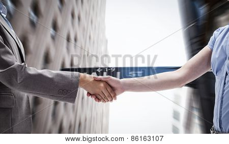 Handshake between two women against wall street