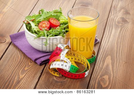 Healthy salad, orange juice and tape measure on wooden table