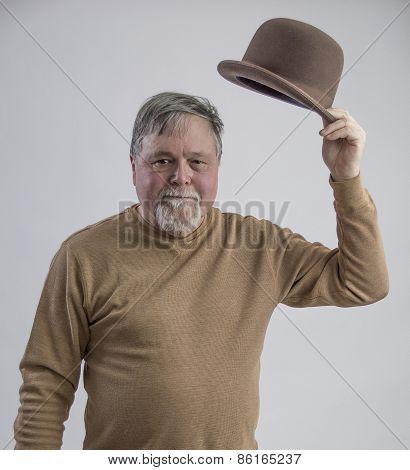 Older Gentleman In Brown Shirt Doffing Brown Derby