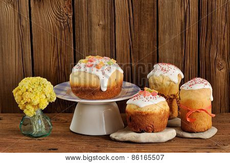 Kulich, Russian Easter Sweet Breads Decorated With Icing And Candied Fruits With Yellow Flowers On W