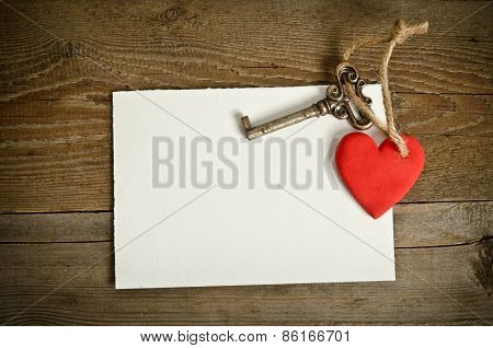 Handmade Heart With Key Together Lying On The Paper For Message On Wooden  Table