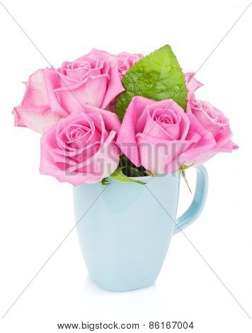 Small pink rose flowers bouquet in tea cup. Isolated on white background