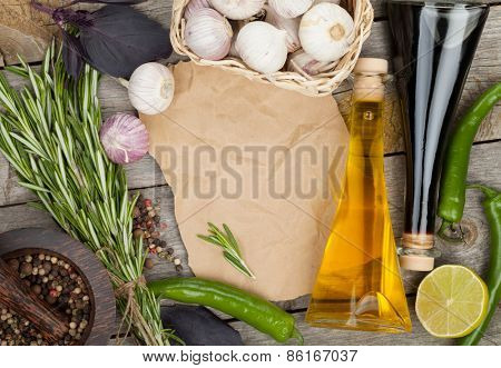 Herbs, spices and seasoning with utensils over wooden table background with paper copy space