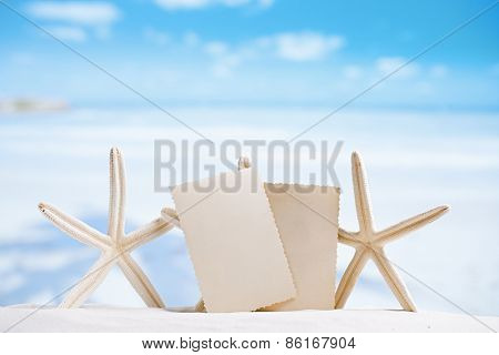 white starfish with blank retro photo on white sand beach, sky and seascape, shallow dof