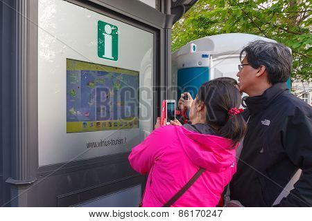 Asian tourists near interactive information scoreboard in the street of Vilnius