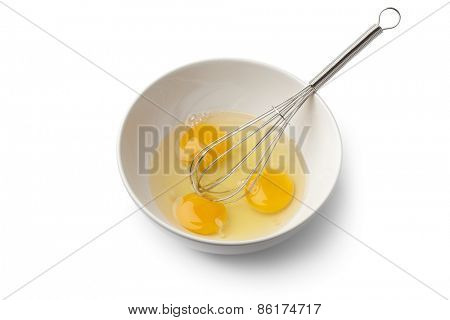 Egg yolks in a bowl with whisk on white background