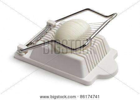 Boiled egg in an egg slicer on white background